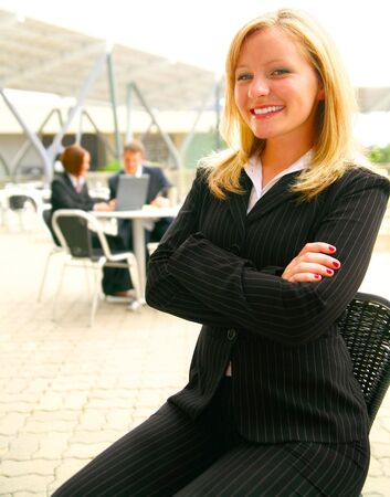 smiling business woman folding hand with two of her coworkers on the background Stock Photo - 3413191