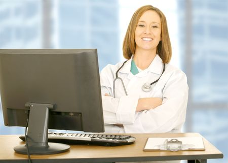 doctor woman sitting on her office with smile and looking to camera. computer set and clip board on her table photo