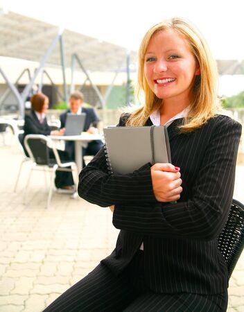 business woman holding note with happy expression sitting outdoor with two of her associates on the background photo