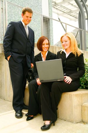 three business people paying attention to laptop as looking on online conference meeting
