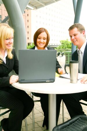 blond business woman showing laptop to her two associates outdoor with cafe setting photo