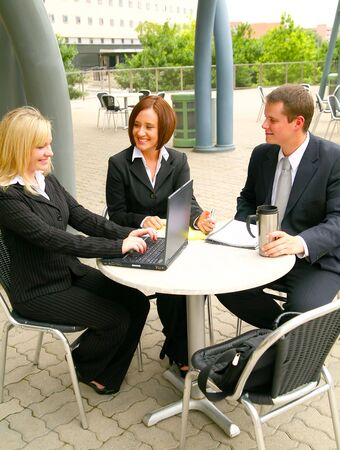 three business people working together. the blond woman is typing on laptop. outdoor with cafe setting
