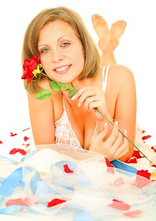 beautiful caucasian bride in lingerie laying on her gown holding red rose and smiling Stock Photo - 3484181