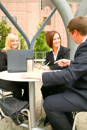 three business people working outdoor in cafe setting