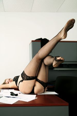 y secretary laying down on her desk and lifting up her legs