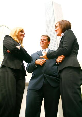 three business people discuss as a team outdoor with tall downtown building on the background Stock Photo - 3557778