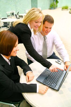blond business woman pointing laptop to two of her associates. taken outdoor in cafe settings area