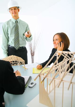 successful contractor about to presenting his work to two business women on table Stock Photo