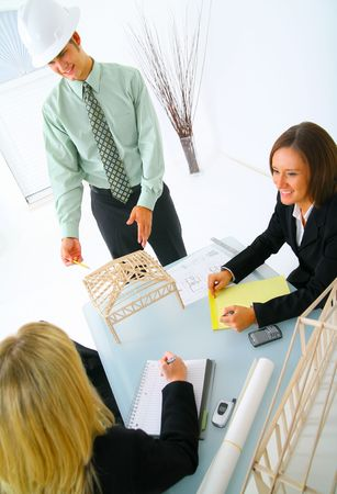 happy caucasian contractor showing house model to two businesswoman. concept for architecture and construction Archivio Fotografico