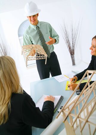 happy caucasian contractor showing house model to two businesswoman. concept for architecture and construction photo