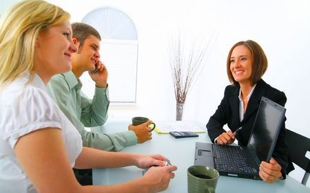 businesswoman in suit showing laptop to professional young couple. concept for purchasing property, car, or investment
