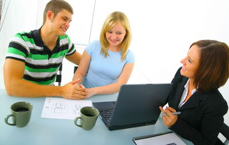 real estate broker showing a laptop to young caucasian couple before they purchase a house Archivio Fotografico