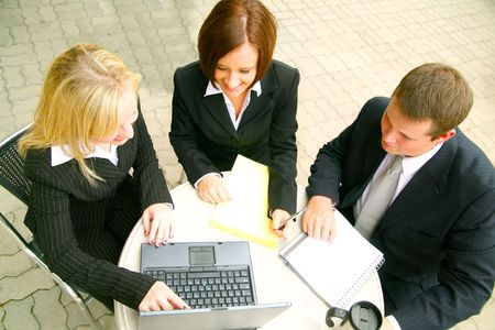 top view of blond business woman pointing at laptop, two other business people paying attention