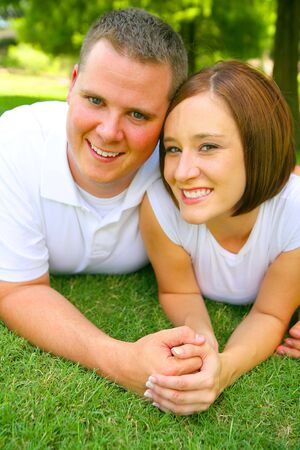 happy caucasian couple laying on grass and holding hand with smile. concept for happiness and Stock Photo - 3673351