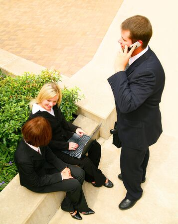 business team working outdoor. the business man standing and receiving phone call while two other business women working on laptop