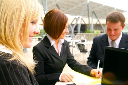 close up of blond woman with happy expression, background showing her two associates working together as a team