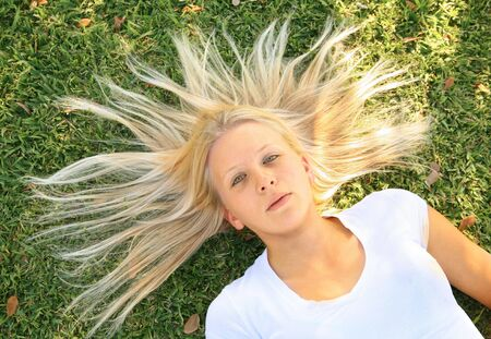 pretty caucasian woman model lay on grass with her hair spread out