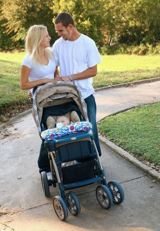 young caucasian parent walking their baby outdoor in park photo