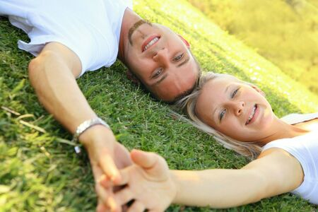 beauty young caucasian couple laying on grass holding hand Stock Photo - 3816598