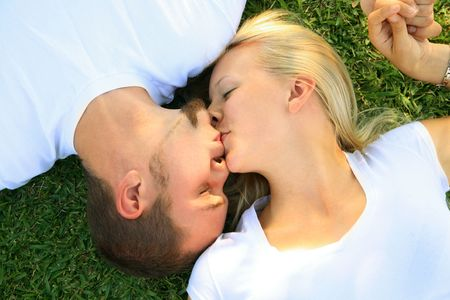 young caucasian couple sharing their love by kiss photo