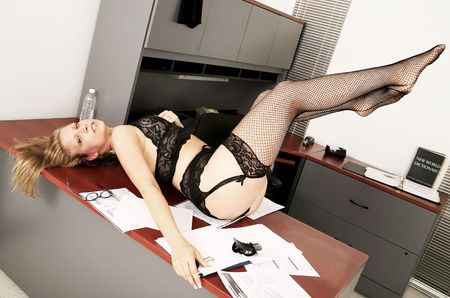 sexy secretary doing messing on her office table photo