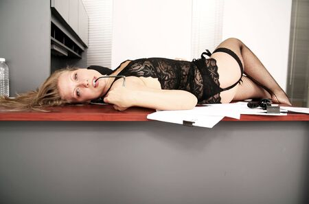 sexy secretary laying down on her desk and biting her glasses photo