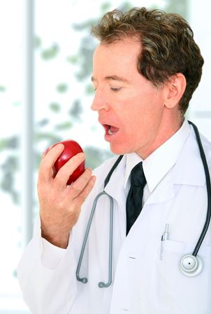 senior doctor eating red apple inside hospital. concept for healthy eating or lifestyle photo