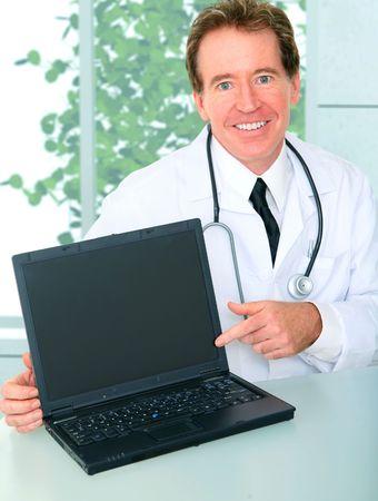 smiling senior caucasian doctor point to his empty blank laptop screen Archivio Fotografico