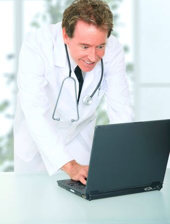 senior caucasian doctor typing on laptop in his office photo