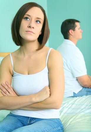couple au lit: deux caucasian jeune homme et la femme avec l'expression triste de mariage trouble