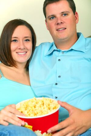two caucasian man and woman couple enjoying movie and popcorn photo
