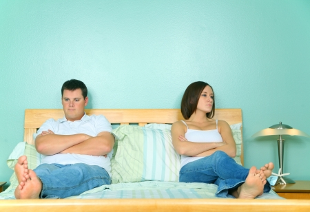 couple bed: upset and angry two caucasian young male and female sit on bed with family problem Stock Photo