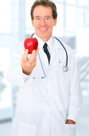 senior doctor caucasian offering red apple to viewer with happy expression photo