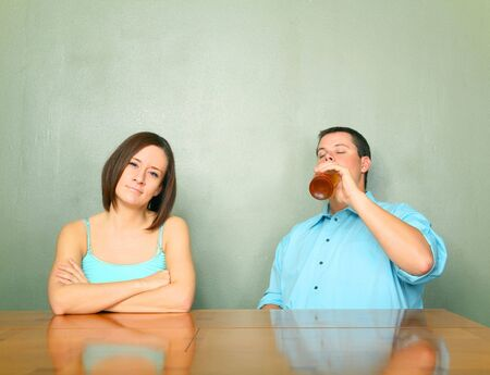 disappointed caucasian female toward her boyfriend or husband drinking problem photo