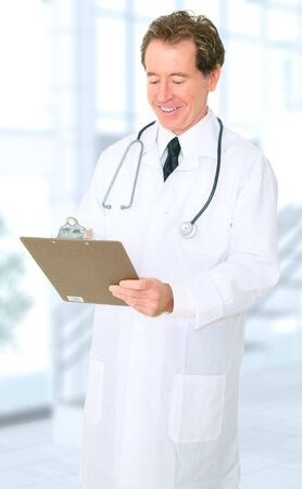 senior happy caucasian doctor writing up report on his clipboard photo