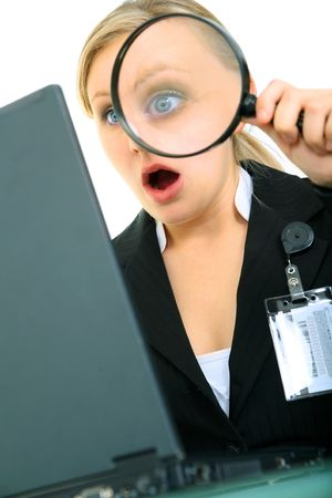 shocked or suprised business woman looking at computer using loupe Stock Photo