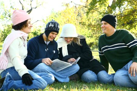 four young caucasian male and female talking and having fun in park photo