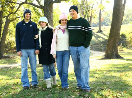 four happy young male and female caucasian walking outdoor in park. concept for family and happiness photo