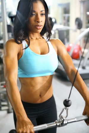 tricep: african american woman training or exercising in gym doing hand pull for tricep with intentional glare