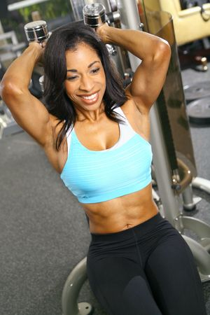 tummy: african american woman training or exercising in gym, weight lifting for tricep Stock Photo