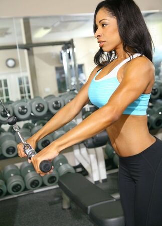 african american woman training or exercising in gym, doing hand pull for tricep. very slight noise on background area Stock Photo