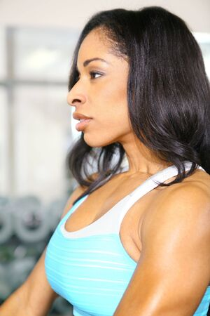 close up pretty african american woman training or exercising in gym photo
