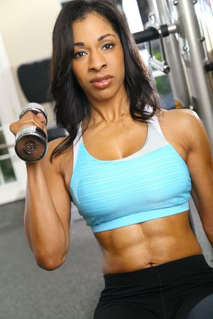 african american woman training or exercising in gym, doing weight lifting photo