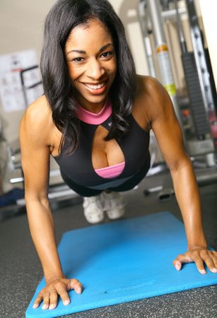 tricep: african american woman training or exercising in gym, doing push up on mattress. very slight noise on background area