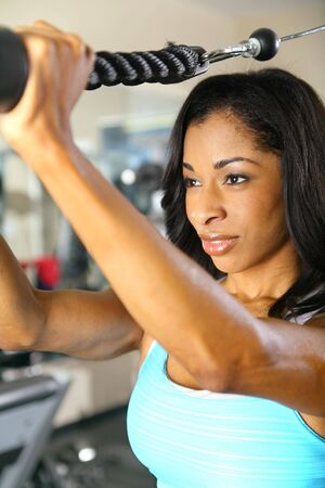 tricep: close up of african american woman training or exercising in gym. very slight noise on background area