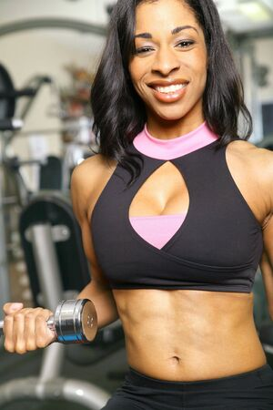 african american woman training or exercising in gym, doing weight lifting. very slight noise on background area Banco de Imagens