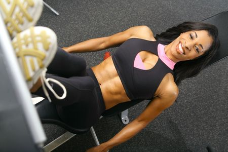 african american woman training or exercising in gym, doing leg press