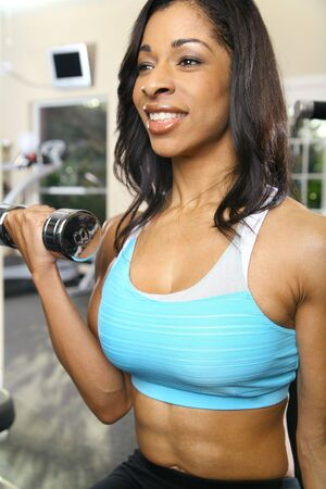 lb: african american woman training or exercising in gym, doing weight lifting. very slight noise on bottom left area