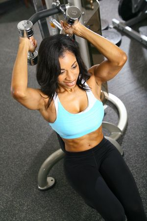 female muscle: african american woman training or exercising in gym, weight lifting for tricep Stock Photo