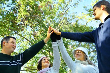 four young male and female friends join hands and lift up in park environment. concept for unity